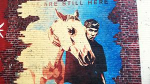 "mural of man with horse with words ""we are still here"""